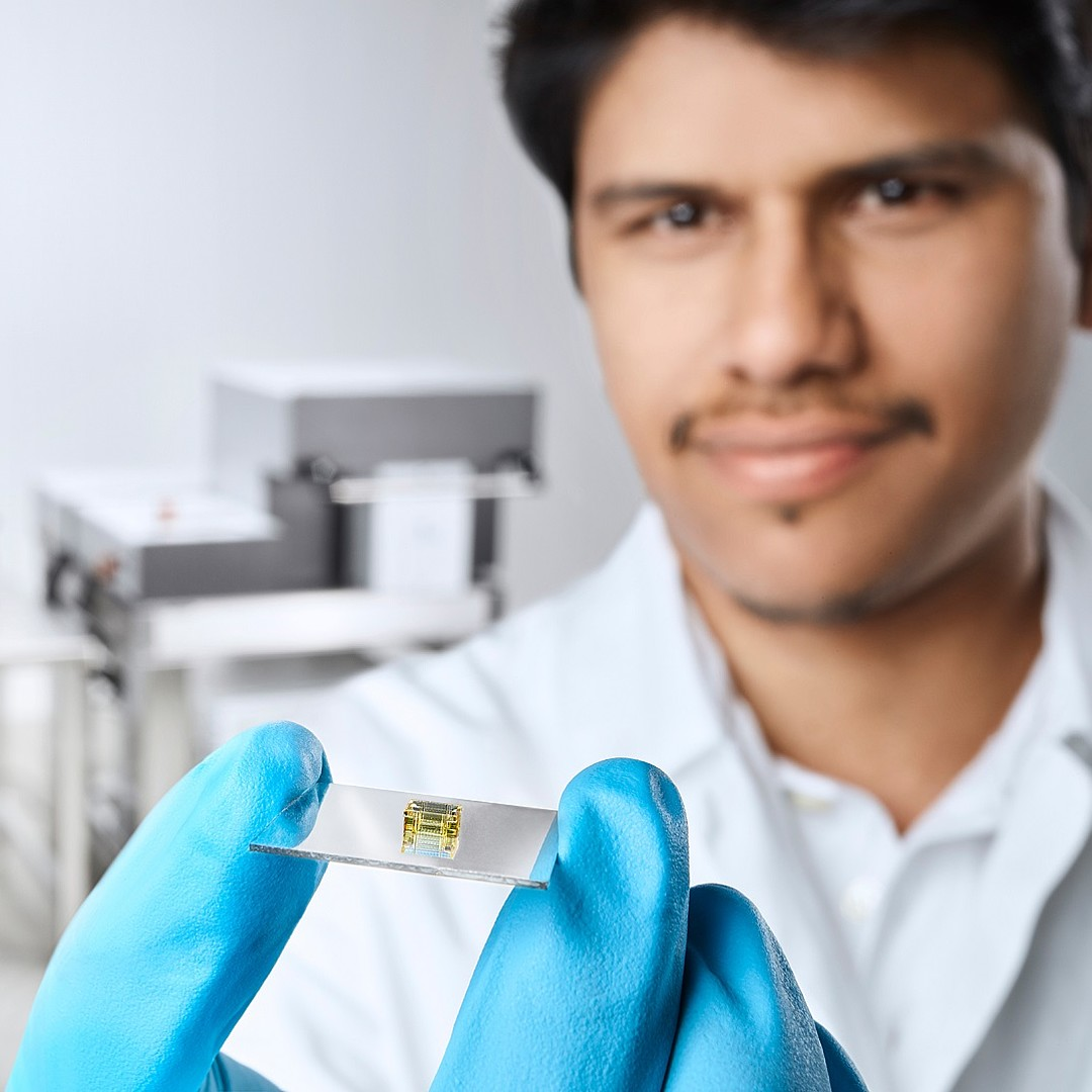 Man holding a 3D printed sample. Nanoscribe's Photonic Professional GT2 in background.